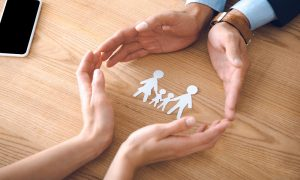 Collaborative family lawyer with open hands showing illustration of family.